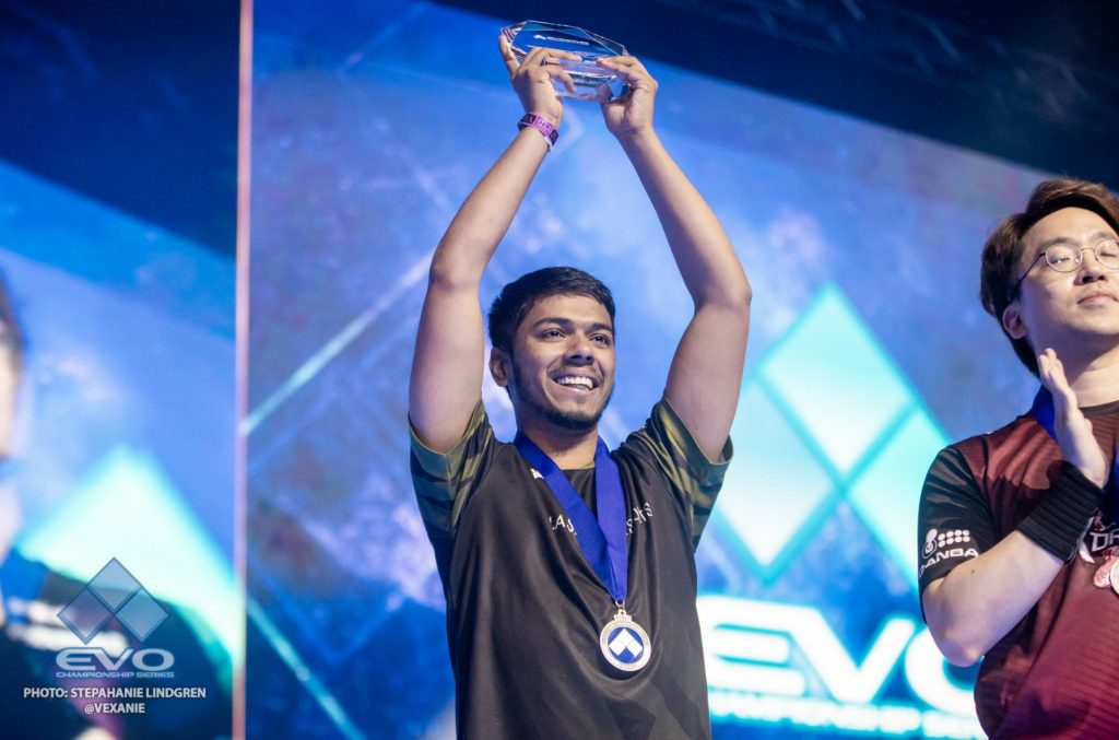 Arslan Ash wins the Tekken (E-sports) tournament called EVO and raises his trophy in celebration.