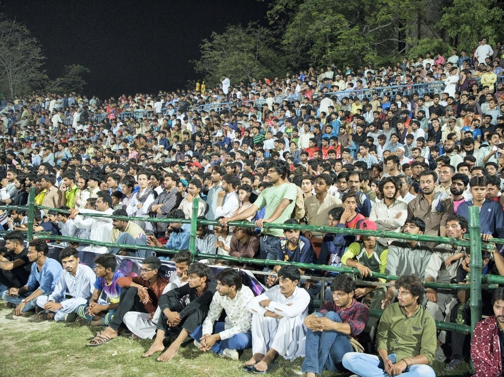 Fans attend to watch a tape ball cricket match