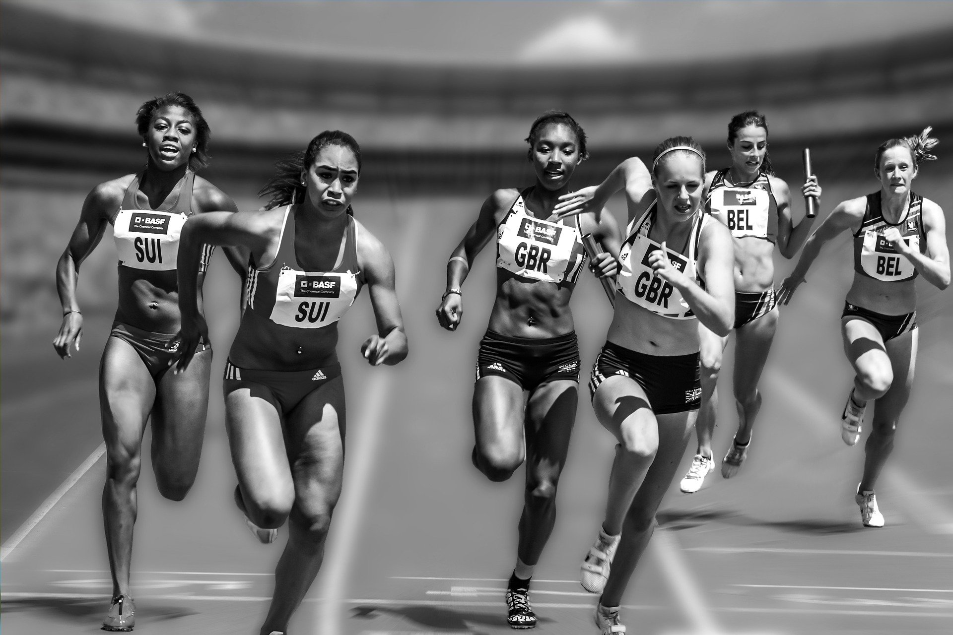 Athletes in a relay race in black and white as a part of competitive sports