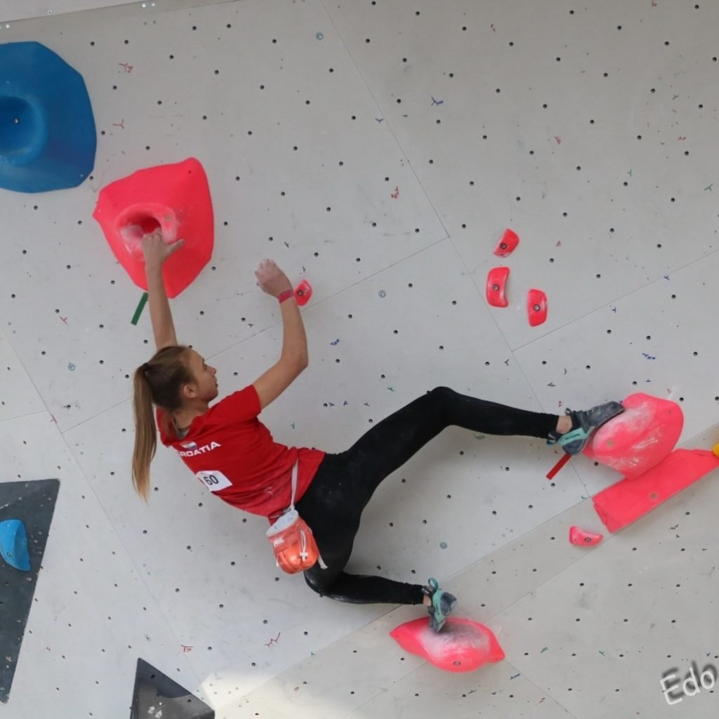anja santini mikulic bouldering on overhanging wall in climbing gym