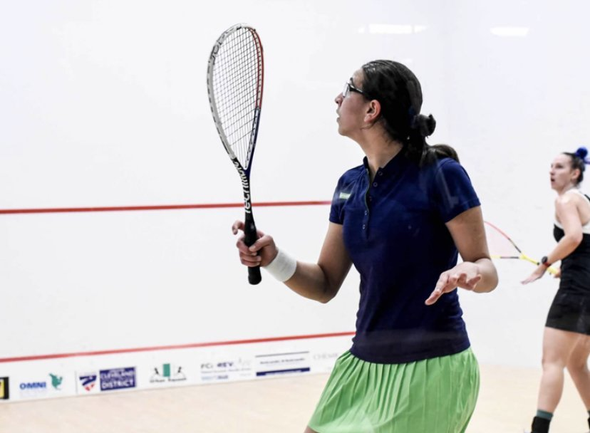 Farida Mohamed strikes the ball, with racquet in hand