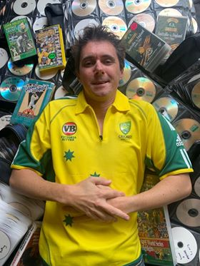 Rob Moody wearing the Australian cricket Jersey lying in front of his recordings of games