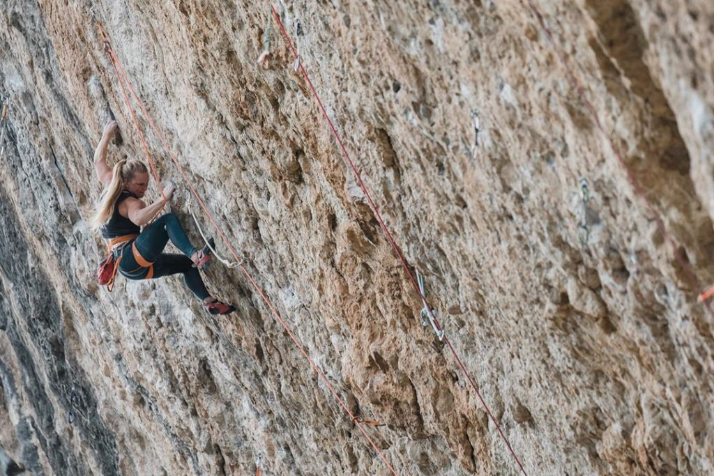 female rock climber ascending on rock wall