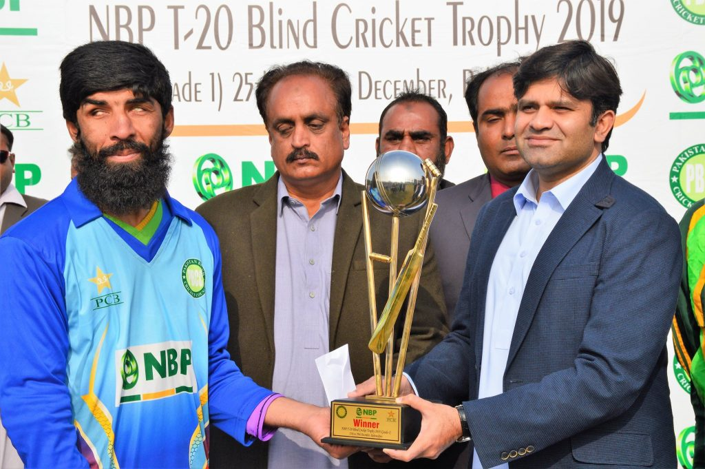 sultan shah gives a trophy to the winning captain of the NBP T-20 Blind Cricket Trophy 2019